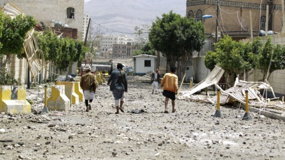 © Mohammed Huwais, AFP | Yemenis walk along a damaged street following a raid by Saudi-led coalition warplanes on a nearby missile depot on Fajj Attan hill in southern Sanaa, on April 20, 2015