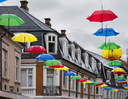 Umbrellas of various colours hanging over Vestergade, Viborg, Denmark. The photo was taken during heavy rain. It was composed from three photos to achieve a balance of light, exposure as well as size.